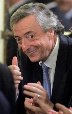 Former Argentine President Nestor Kirchner gestures as he arrives for a ceremony at the Casa Rosada Government Palace in Buenos Aires, June 17, 2008. Kirchner's wife Argentine President Cristina Fernandez's image deteriorated further in June as a nasty dispute with the farm sector entered its fourth month, according to a poll released on Tuesday. Her center-left government raised soy export taxes in mid-March, sparking farmer protests that have caused occasional food and fuel shortages. REUTERS/Marcos Brindicci (ARGENTINA)